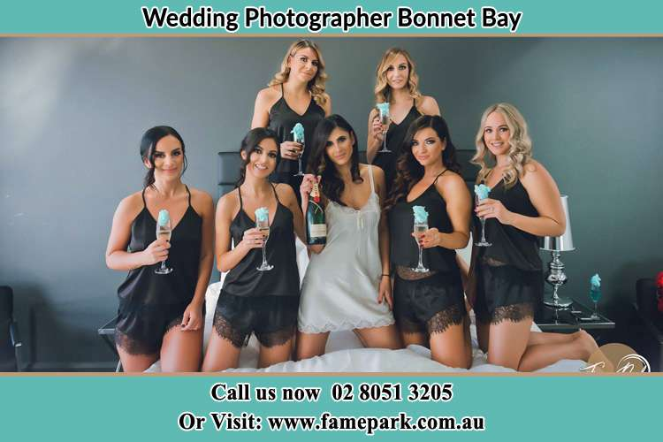 Photo of the Bride and the bridesmaids wearing lingerie and holding glass of wine on bed Bonnet Bay NSW 2226