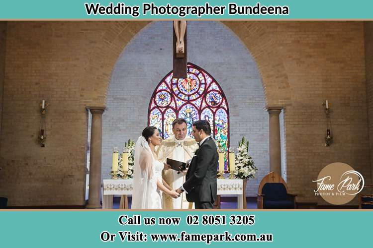 Photo of the Bride and Groom at the Altar with the Priest Bundeena NSW 2230