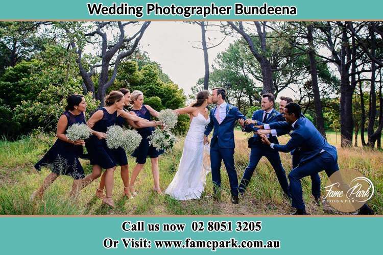 Photo of the Bride and the Groom kissing while teasing by the entourage Bundeena NSW 2230