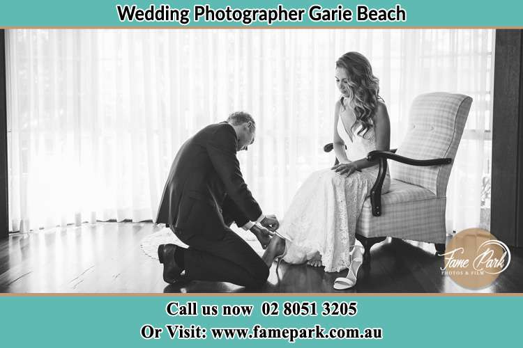 The Bride is being helped by the Groom trying to put on her shoes Garie Beach NSW 2233