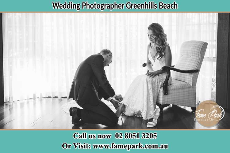The Bride is being helped by the Groom trying to put on her shoes Greenhills Beach NSW 2230