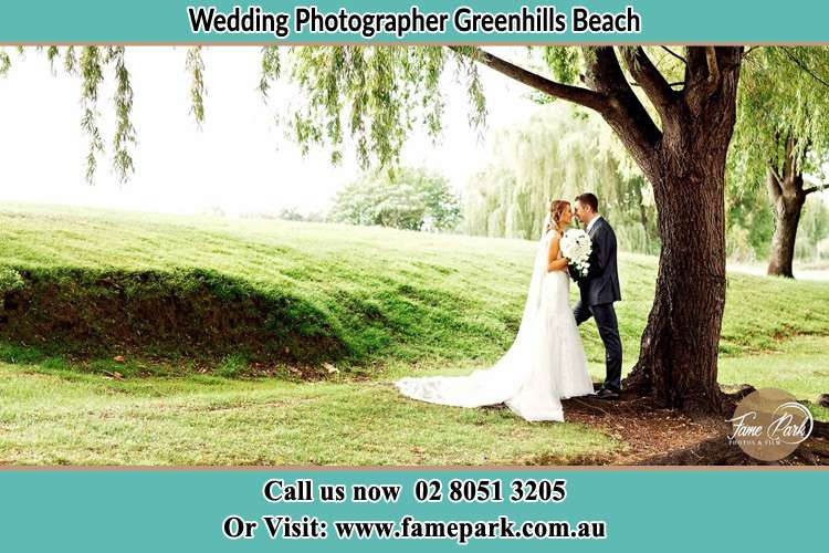 Photo of the Bride and the Groom kissing under the tree Greenhills Beach NSW 2230