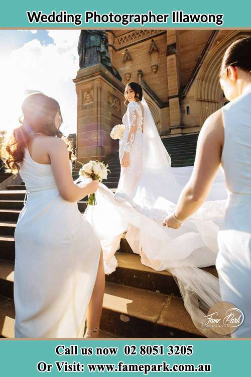 Photo of the Bride smiling on the bridesmaid holding the tail of her wedding gown at the front of the church Illawong NSW 2234