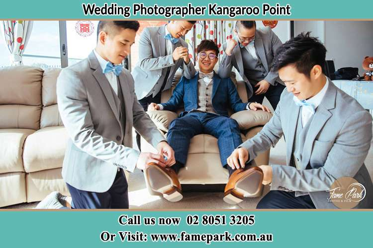 Photo of the Groom helping by the groomsmen getting ready Kangaroo Point NSW 2224