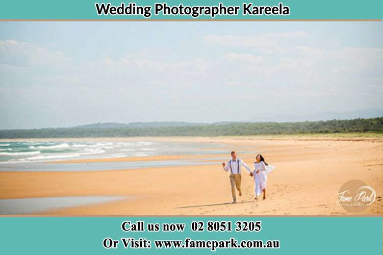 Photo of the Groom and the Bride walking at the sea shore Kareela NSW 2232
