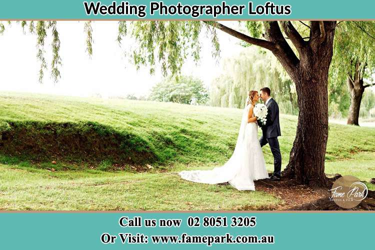 Photo of the Bride and the Groom kissing under the tree Loftus NSW 2232