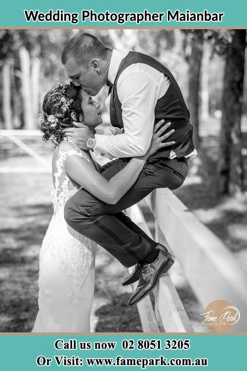 Photo of the Groom sitting on the fence while kissing the Bride on the forehead Maianbar NSW 2230