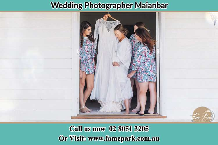 Photo of the Bride and the bridesmaids checking the wedding gown at the front door Maianbar NSW 2230
