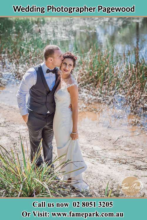 Photo of the Groom kiss the Bride near the lake Pagewood NSW 2035