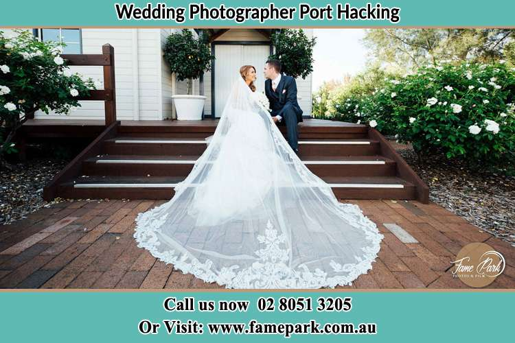 Photo of the Bride and the Groom looking each other while sitting at the staircase Port Hacking NSW 2229