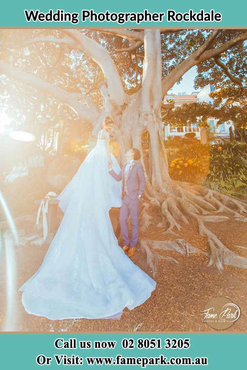 Photo of the Bride and the Groom looking each other besides the tree Rockdale NSW 2216