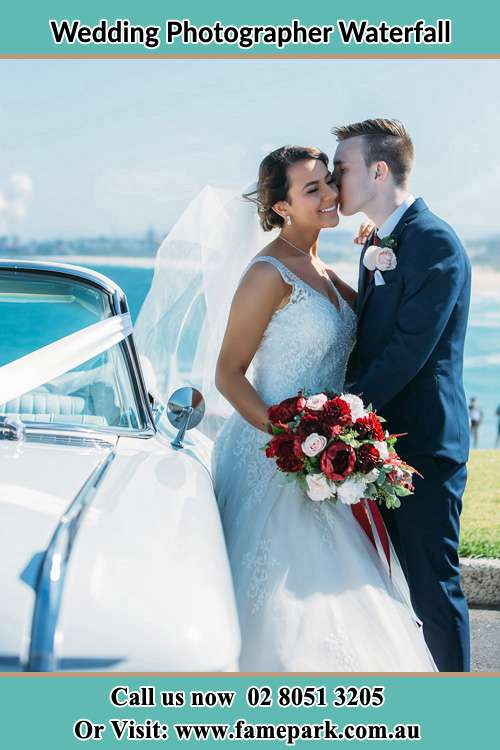 Photo of the Groom kiss the Bride besides the bridal car Waterfall NSW 2233